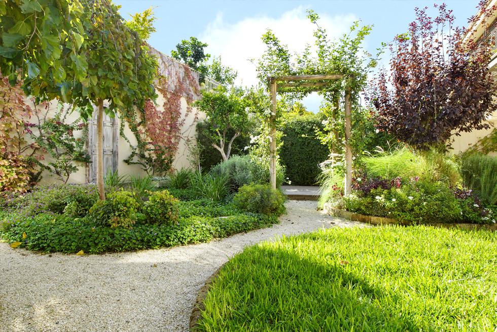 מעבר מקורה בגינה האורבנית הבנוי מסנדות עץ וצמחיה מטפסת, צילום: מושי גילטיס